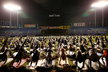 Participants practice yoga during an evening yoga event to promote a healthier lifestyle at a baseball stadium in Tokyo