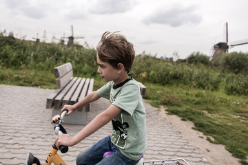 Boy bikes through Holland