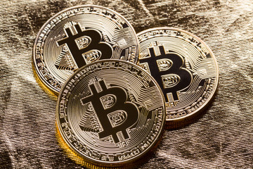 Bitcoin coins on gold colour background.
