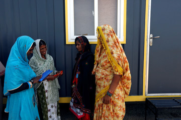Women trainees talk outside of their classroom after attending a training session of the Female Dump Truck Driver Programme, held by the Sindh Engro Coal Mining Company, in Islamkot