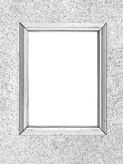 An empty frame hangs on the wall, a black and white pattern.