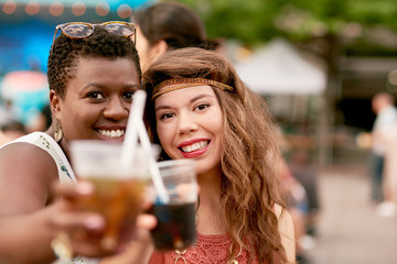 Diverse group of two girls having a drink in the crowd of a summer music festival