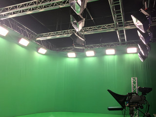 Modern empty green video recording and broadcasting studio with tv channel led screen and metalic stands, lights on