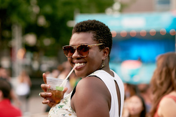Attractive african american girl drinking from a plastic glass in the crowd of a summer music festival