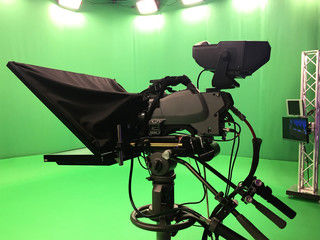 Modern empty green video recording and broadcasting studio with tv channel led screen and metalic stands, text prompter, lights on