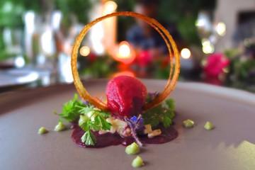 fruit sorbet dessert with spun caramelized sugar on candlelit table