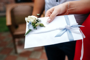 White wedding envelope with a boutonniere in the hand of a woman. A gift from the invited guests to the wedding.