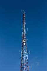 High antenna tower used for various signals and blue sky in background.