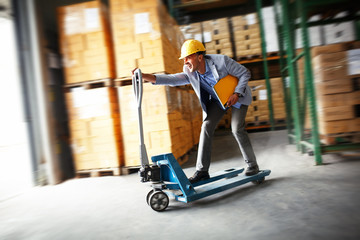 Customs manager drives forklift in the warehouse.Positive and fun business concept.