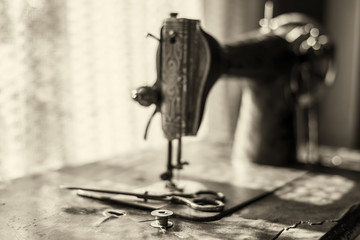 Metal coil with threads in which the needle is inserted and the scissors lie on an old sewing machine against the background of a window through which the sun's rays pass.