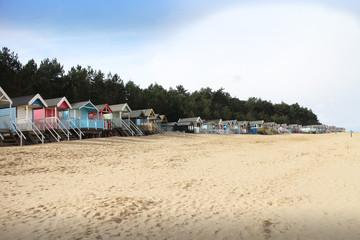 Row of beach huts on an empty, sandy Norfolk beach