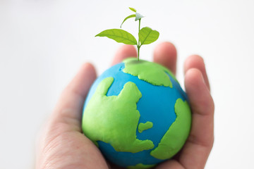 concept of earth day , hand holding earth with small plant