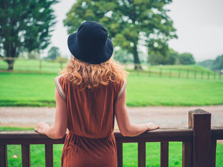 Woman wearing hat relaxing on porch