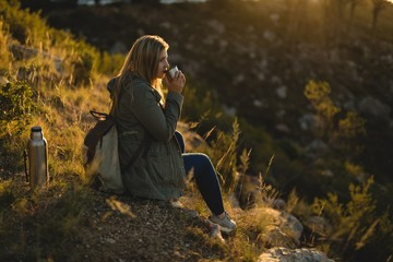 Female hiker having drink while sitting on mountain
