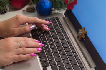 Winter holidays. Chatting and freelance. Unrecognizable woman typing on laptop on festive background, close up picture. Working during Christmas and New Year, greetings in social network concept