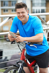 Young Man Using Mobile Phone Whilst Out On Cycle Ride In Urban Setting