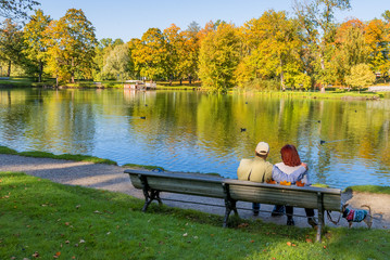 Happy couple of seniors are resting on the wooden, city public park, the early autumn in Europe