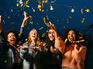 Happy women throwing confetti in the air. Friends celebrating outdoors.