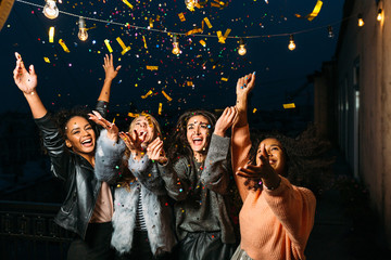 Group of female friends under confetti. Women having fun outdoors.