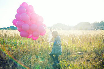 Happy toddler birthday girl in autumn field holding many pink balloons,walking away