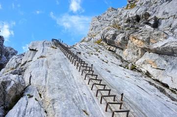 In der vertikalen Kalksteinwand eines Klettersteigs angebrachte Stahl-Steighilfen (Klammern)