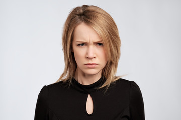portrait of young serious angry woman with blond hair