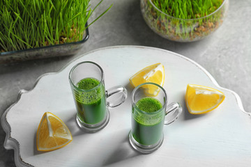 Wheat grass shots and slices of lemon on white board