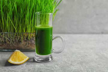 Wheat grass shot and slice of lemon on grey background
