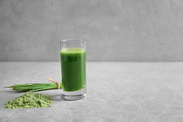 Wheat grass shot and powder on grey background