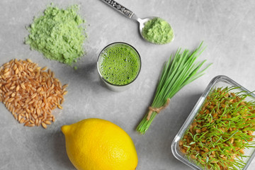 Composition with wheat grass products and lemon on grey background