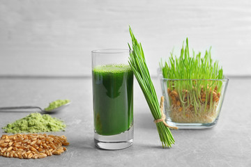 Wheat grass shot and grain on grey table