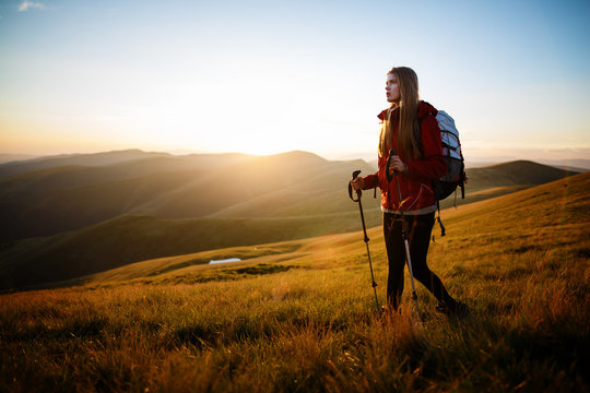 Shot of a young woman looking at the landscape while hiking in the mountains. Happy traveler with backpack standing on top of a mountain and enjoying sunset view