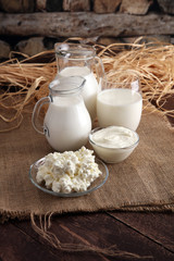 Foto op Textielframe Zuivelproducten milk products. tasty healthy dairy products on a table on. sour cream in a bowl, cottage cheese bowl, cream in a a bank and milk jar, glass bottle and in a glass