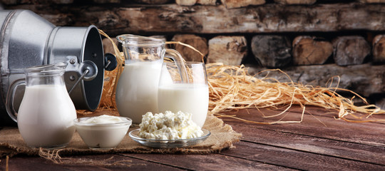 Fotorolgordijn Zuivelproducten milk products. tasty healthy dairy products on a table on. sour cream in a bowl, cottage cheese bowl, cream in a a bank and milk jar, glass bottle and in a glass