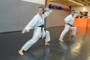man and woman in white kimono black belt training karate