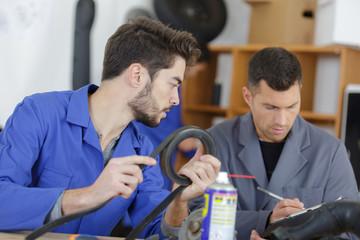 apprentice mechanic holding pipe