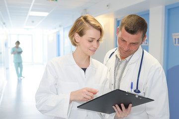 two doctors with clipboard at hospital corridor