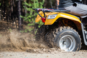 An ATV quadbike get stuck in a sandy road near forest and having wheel-spin making a spray of sand