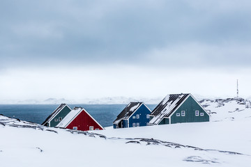 Four colorful inuit houses among therocks in a suburb of arctic capital Nuuk, Greenland