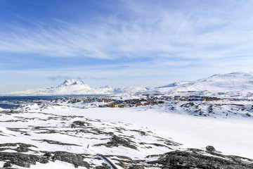 Nuuk city suburb at the fjord, snow landscape with blue sky and Sermitsiaq mountain in the background, Greenland