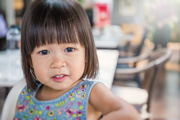 Portrait of little cute asian girl, lovely small asian girl with her hands holding her cheeks, happy and fun expression, close up