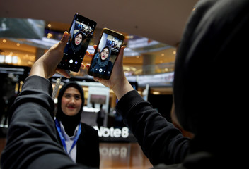 A customer takes selfie pictures using Samsung Galaxy Note 8 (L) and Galaxy Note 5 during the consumer launch event in Jakarta