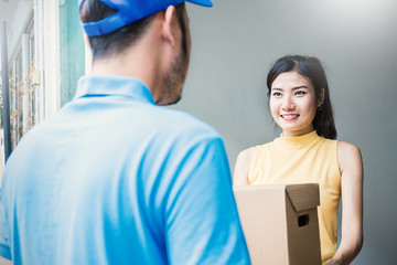 Asian woman accepting receive a delivery of boxes from delivery asian man, sign and receive delivery concept