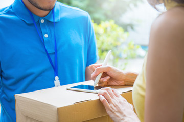 woman accepting receive a delivery of boxes from delivery asian man, sign and receive delivery concept