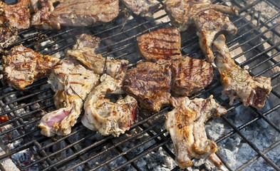 Sausages and steaks being grilled on a barbecue