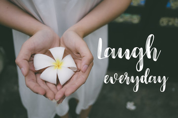 Life quote. Inspirational quote on the girl holding white flower. Laugh everyday.