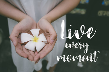 Life quote. Inspirational quote on the girl holding white flower. Live every moment.
