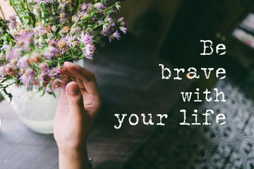 Life quote. Motivation quote on soft background. The hand touching purple flowers. Be brave with life.