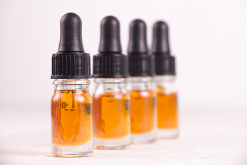 Vials of CBD oil, cannabis live resin extraction isolated on white - medical marijuana concept