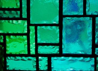 Ausschnitt aus einem geometrischen Buntglasfenster in Grün- und Blautönen